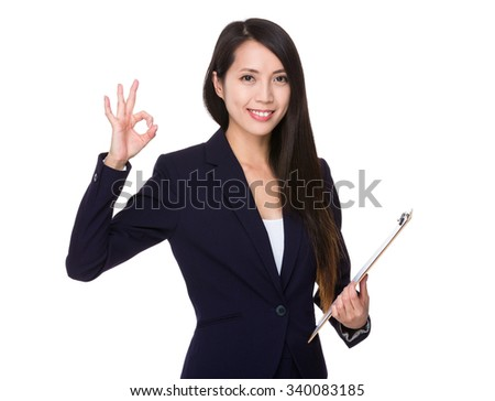 Businesswoman hold with clipboard and ok sign gesture - stock photo