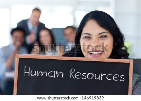 Businesswoman holding a blackboard with human resources written on it - stock photo