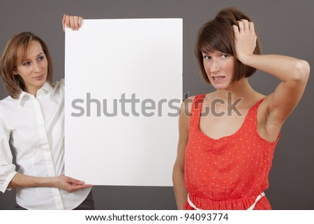 businesswoman holding a blank white board selling or showing something, another woman finds it hard to make a decision. - stock photo