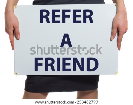 Businesswoman holding a card with a motivational message written on it Refer a friend - stock photo