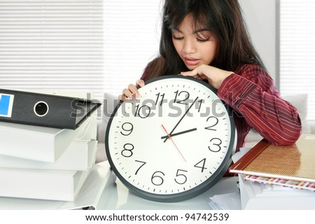 businesswoman holding a clock. dateline stress at work concept - stock photo