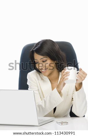 Businesswoman holding a coffee mug and looking at a laptop