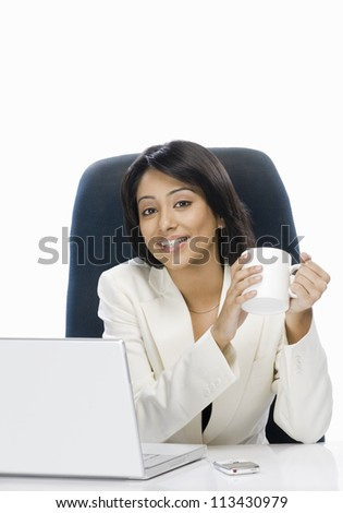 Businesswoman holding a coffee mug and smiling - stock photo