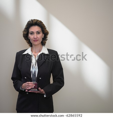 Businesswoman holding a glass trophy - stock photo