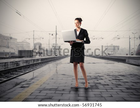 Businesswoman holding a laptop on the platform of a train station