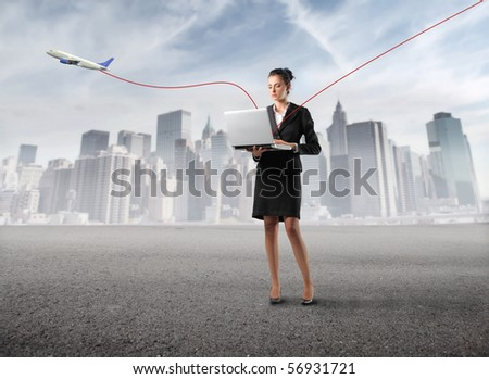 Businesswoman holding a laptop with a cityscape and a plane on the background - stock photo