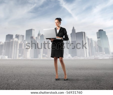 Businesswoman holding a laptop with cityscape on the background - stock photo