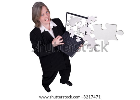 Businesswoman holding a laptop with puzzle pieces flying out with a funny expression isolated over white - stock photo