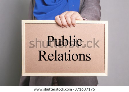 Businesswoman holding a softboard written Public Relations - stock photo
