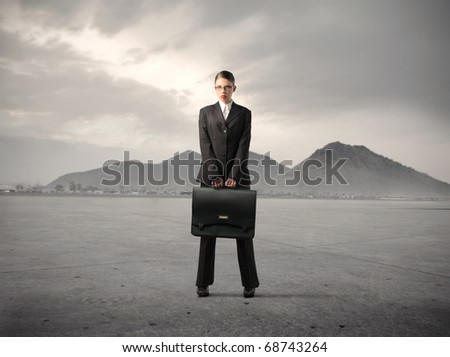 Businesswoman holding a suitcase in a desert