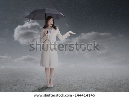 Businesswoman holding an umbrella during a stormy weather