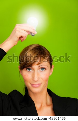 Businesswoman holding as professional 2 lightbulbs in white and yellow as conceptual symbol of businessperson successful innovation and ecological treatment - stock photo