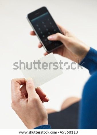 businesswoman holding blank business card and dialing numbers on mobile phone - stock photo