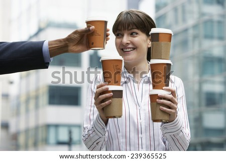 Businesswoman Holding Coffees Outside Office Building - stock photo