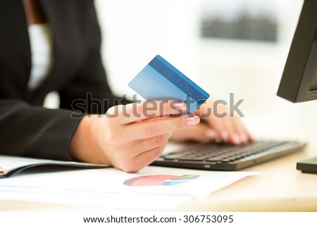 Businesswoman holding credit card in hand and entering security code using laptop keyboard - stock photo