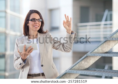 Businesswoman holding digital tablet and showing ok sign. - stock photo