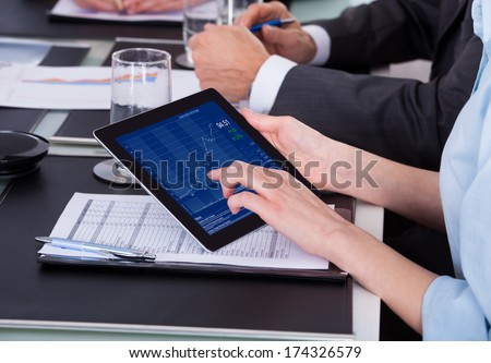 Businesswoman Holding Digital Tablet Over Graph Sitting At Desk - stock photo
