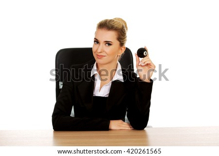 Businesswoman holding eight billiard ball by a desk - stock photo
