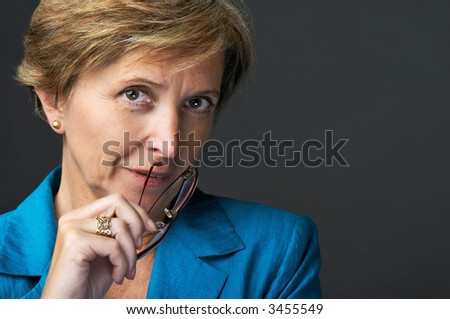Businesswoman holding glasses looking at camera, close-up portrait - stock photo