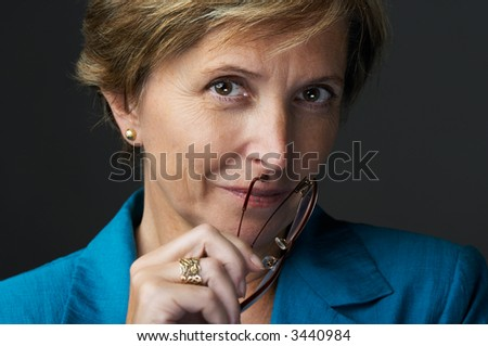 Businesswoman holding glasses looking at camera, portrait - stock photo