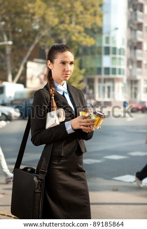 businesswoman holding her breakfast and going to work, outdoor - stock photo
