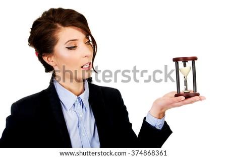 Businesswoman holding hourglass. - stock photo