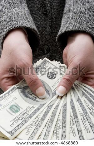 Businesswoman holding hundred dollar bills - stock photo