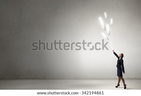 Businesswoman holding in hand bunch of light bulb balloons - stock photo