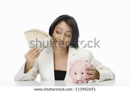 Businesswoman holding Indian paper currency and piggy bank - stock photo