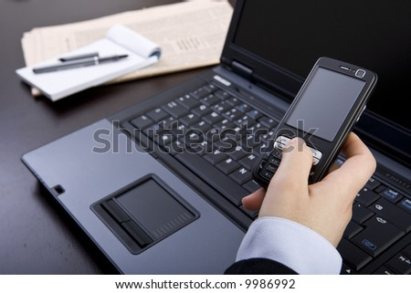 businesswoman holding mobile phone in office