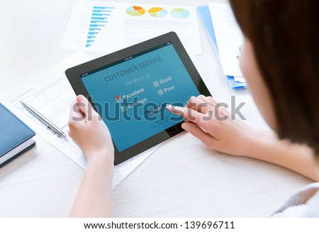Businesswoman holding modern digital tablet with customer service survey form on a screen. Red tick on excellent choice showing customer satisfaction - stock photo