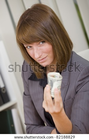 businesswoman holding money in her hand by office work