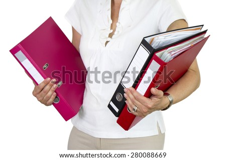 Businesswoman holding onto a tall stack of office binders  - stock photo