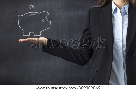 Businesswoman holding piggy bank drawing front of blackboard - stock photo