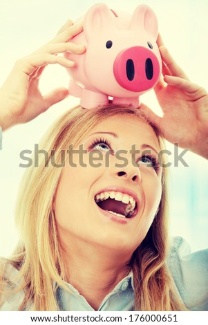 Businesswoman holding piggy bank. Over abstract blue background  - stock photo