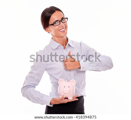 Businesswoman holding pink porcelain piggy bank with a very satisfied toothy smile and a thumb up gesture wearing her hair back and a button down shirt while looking at camera on a white background - stock photo