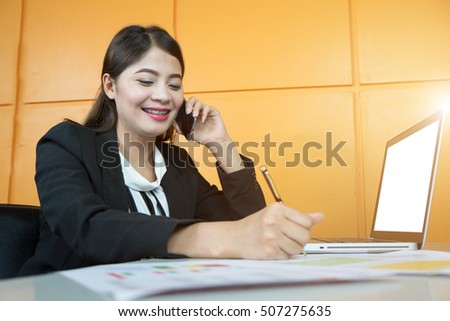Businesswoman holding smart-phone at office with laptop and document on table.