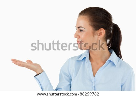Businesswoman holding something up and looking at it against a white background - stock photo