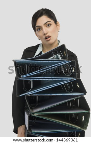 Businesswoman holding stack of binders - stock photo