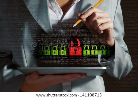 Businesswoman holding tablet pc entering password. Security concept - stock photo