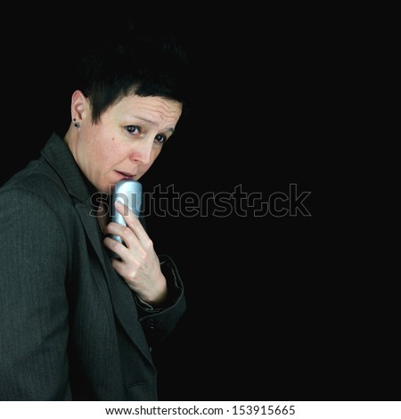 Businesswoman holding telephone handset by her mouth, worried about making or receiving a difficult call. Against black background. - stock photo