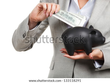 Businesswoman holding the piggy bank and dollar bills in her hands - stock photo