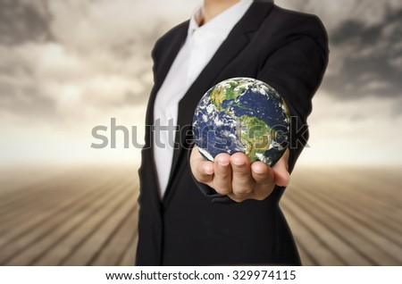 Businesswoman holding the world, Elements of this image furnished by NASA.