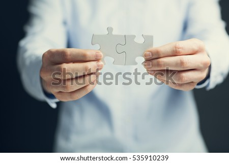 Businesswoman holding two matching jigsaw puzzle pieces together. Shallow focus.