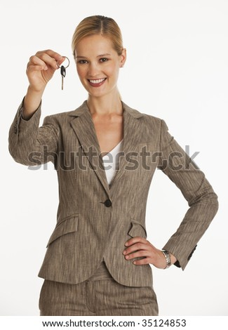 businesswoman holding up a pair of keys towards the camera