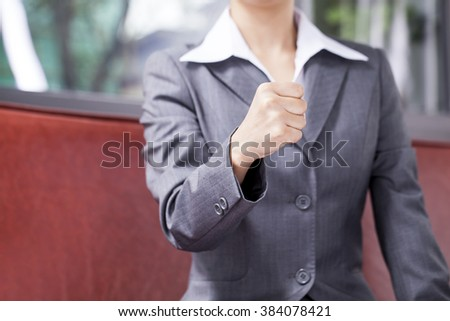 Businesswoman holding up her fist. - stock photo