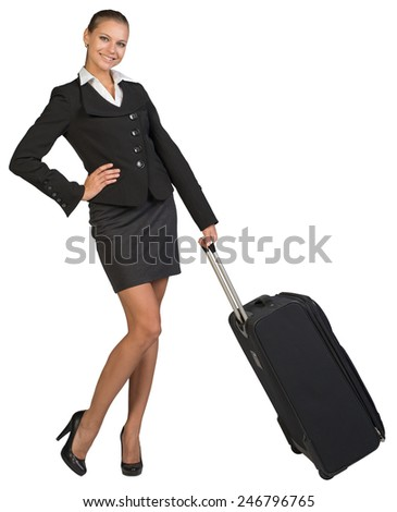 Businesswoman holding wheeled bag, hand on hip, looking at camera, smiling. Isolated over white background