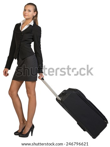 Businesswoman holding wheeled bag in moving position, looking at camera, smiling. Isolated over white background