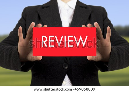 Businesswoman in a black jacket shows a card with the inscription review. Selective focus. - stock photo