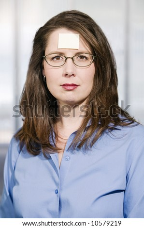 Businesswoman in a blue shirt with a blank sticky note on her forehead
